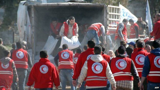 Syrian Arab Red Crescent workers offload aid from a lorry as Syrians evacuated from rebel-controlled districts that were besieged by the army, arrive at a government-ruled area, in the central Syrian city of Homs, on Wednesday
