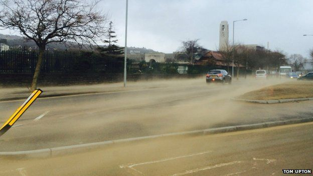 Sand is blown across Mumbles Road and beyond during strong winds in Swansea