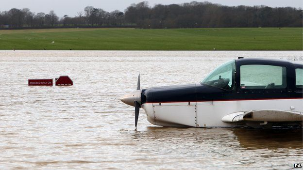 A plane sits in flood water at Redhill aerodrome after heavy rain
