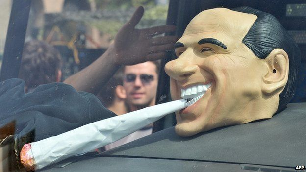 A mask of Italy's Prime Minister Silvio Berlusconi smoking a joint is displayed in a van during the Million Marijuana March on 9 May 2009 in Rome.
