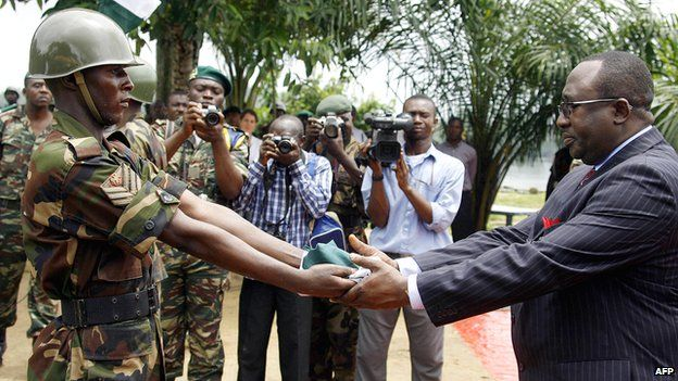 A Nigerian soldier presents a flag after lowering it to Nigerian Justice Minister Bayo Ojo to signify the country's final withdrawal from the Bakassi Peninsula on 14 August 2006