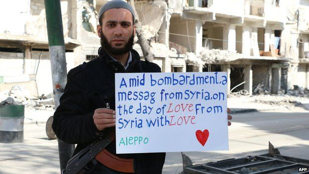 """Rebel fighters in Syria holds placard hailing the """"day of love"""""""