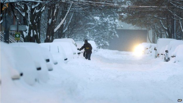 A motorist opens a car door before digging out of snow in Albany, New York on 14 February 2014
