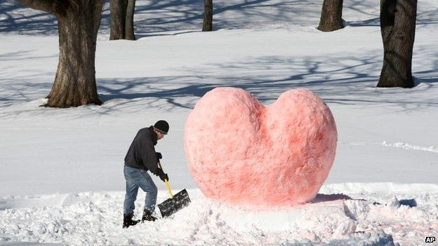Gilberto Lozada of Winchester, Virginia constructs the base of his Valentine's Day snow sculpture in the city's Jim Barnett Park 14 February 2014