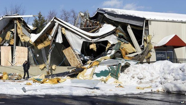 A man stands in front of the collapsed roof at the West Rock Indoor Sports and Entertainment Complex in West Nyack, New York, 14 February 2014