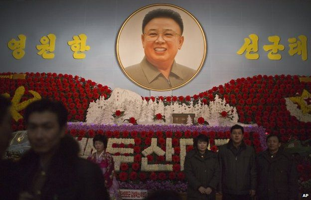 North Koreans pose for family pictures in front of a portrait of the late leader Kim Jong Il during a flower exhibition in Pyongyang, North Korea, Sunday, Feb. 16