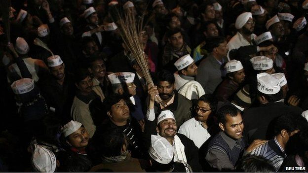 """A supporter of Delhi""""s Chief Minister Arvind Kejriwal, chief of the Aam Aadmi (Common Man) Party (AAP), holds a broom, the party symbol, at the party headquarters in New Delhi February 14, 2014"""