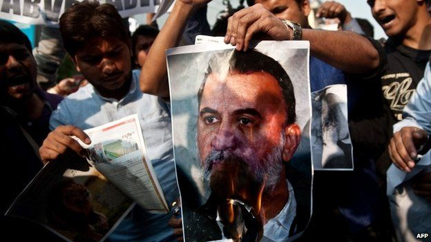 In this photograph taken on November 22, 2013, protesters burn a photograph of Tarun Tejpal, in New Delhi.