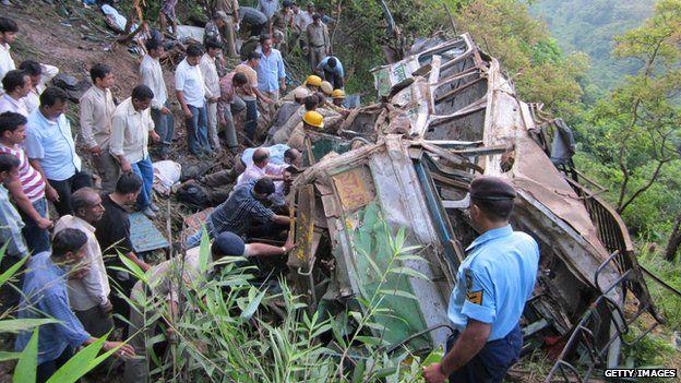 Resuers manhandle crashed bus on Indian hillside