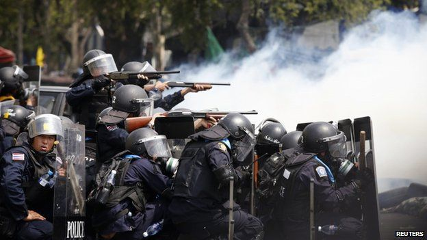 Thai policemen aim their weapons towards anti-government protesters during clashes near Government House in Bangkok, 18 February 2014