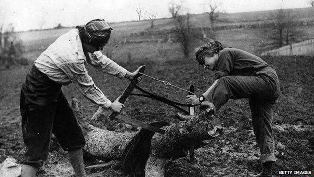 two land girls sawing a log