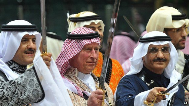 Prince Charles, wearing a traditional Saudi uniform, dances with a sword during traditional Saudi dancing