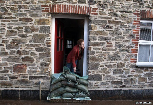 Resident looks out of front door of flooded house