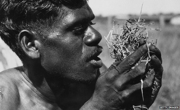An Aborigine blowing into dry grass