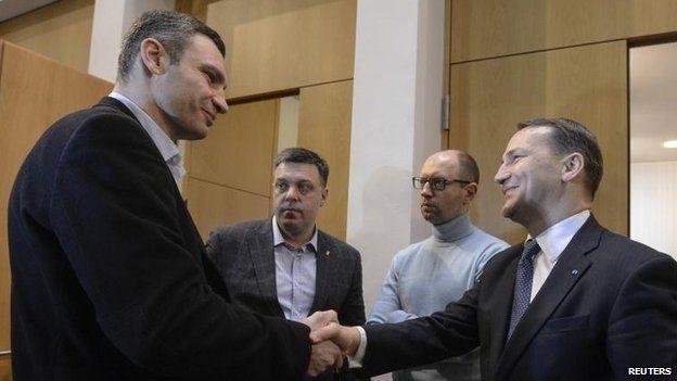 Polish Foreign Minister Radek Sikorski shakes the hand of Ukrainian opposition leader Vitaly Klitschko, as Oleh Tyahnybok and Arseniy Yatsenyuk look on, Kiev (20 Feb)