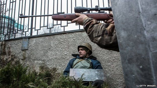 An anti-government protester aims a gun in the direction of suspected sniper fire near the Hotel Ukraine