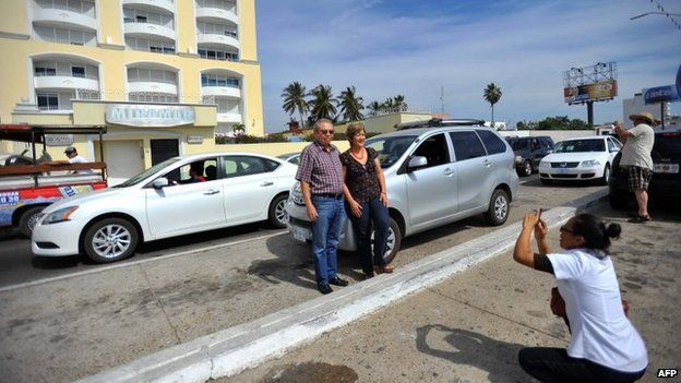 A couple poses for a photo in front of the Miramar apartment block in Mazatlan on 22 February, 2014