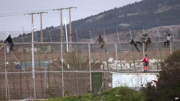 Sub-Saharan migrants climb over a metallic fence that divides Morocco and the Spanish enclave of Melilla, as a Red Cross worker is on-hand to offer humanitarian assistance (17 February 2014)