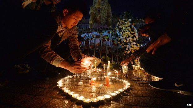 Chinese mourners light candles at the scene of the knife attack at the main train station in Kunming, Yunnan Province on 2 March 2014