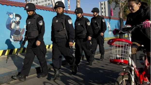 Armed policemen patrol on a street near the Kunming Railway Station in western China's Yunnan province, 3 March 2014