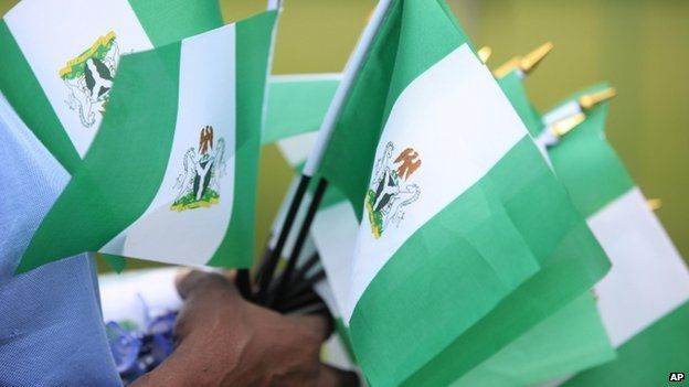 An unidentified woman sells Nigerian national flags, during an event to mark Nigeria independence day, in Lagos, Nigeria. Tuesday 1 October 2013