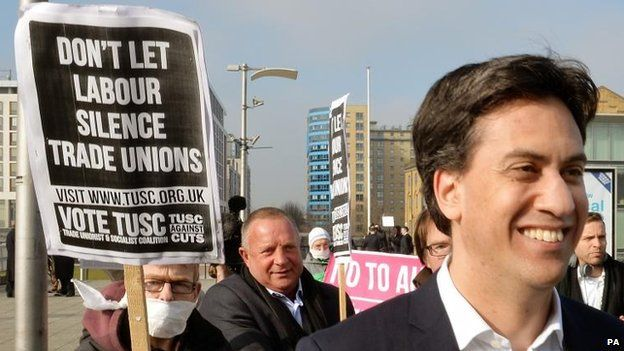Protesters behind Mr Miliband