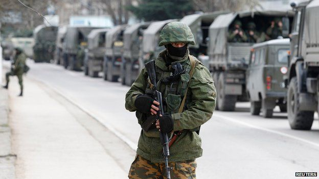 Armed serviceman stands by Russian army vehicles in the Crimean town of Balaclava on 1 March 2014