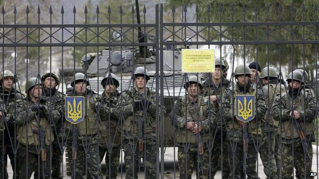 Ukrainian soldiers guard a gate of an infantry base in Perevalnoye
