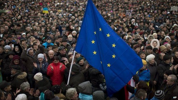 People applaud as the European Union flag is held up by a protester in Kiev