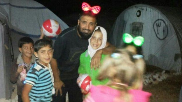 Majeed playing with children in a camp