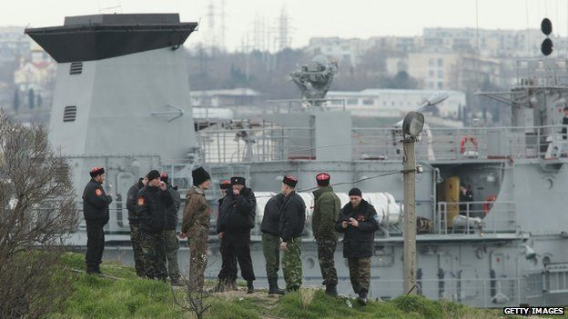 Men dressed as Russian Cossacks stand on a hill guarding access to the Ukrainian naval command ship Slavutych