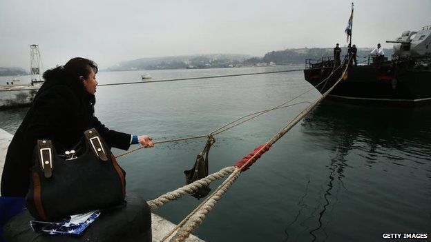 A woman uses a pulley to send food to her husband on board a blockaded Ukrainian warship in Sevastopol harbour (7 March 2014)