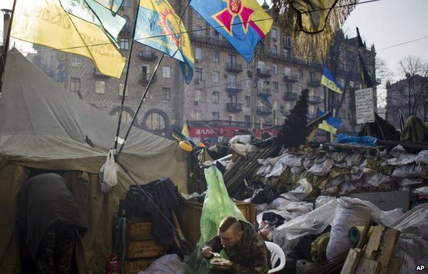 A member of a self-defence group eats breakfast next to a barricade in Kiev's Independence Square (7 March 2014)