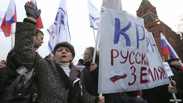"""Protesters carry a banner reading """"Crimea is Russian land!"""" at a rally in Moscow (7 March 2014)"""