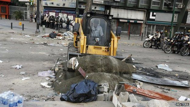 A barricade set by anti-government protesters is removed at Altamira square in Caracas on 6 March, 2014.