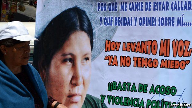 """An activist protests next to a placard saying """"Today I raise my voice, I no longer am afraid"""" at a march in La Paz"""