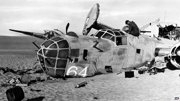 "A member of a search party enters the hulk of the World War II B-24 bomber ""Lady Be Good,"" found in the Libyan desert in May 1959"