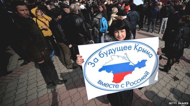 """Pro-Russian demonstrator in Crimea, with sign reading, """"For Crimea's future with Russia"""""""