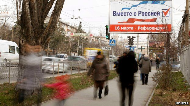 "People walk under a referendum poster reading ""Together with Russia. March 16 - referendum"" in Simferopol on 12 March 2014"