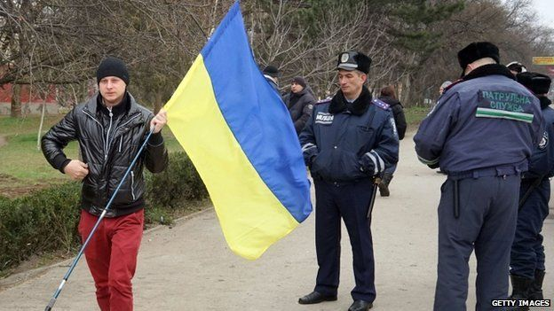 Police officers stand by as a pro-Ukrainian supporter holding a Ukrainian flag parades in Simferopol