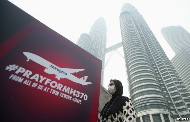 """A woman wearing a mask against the haze walks past a board saying """"Pray for MH370"""" in Kuala Lumpur, March 14"""