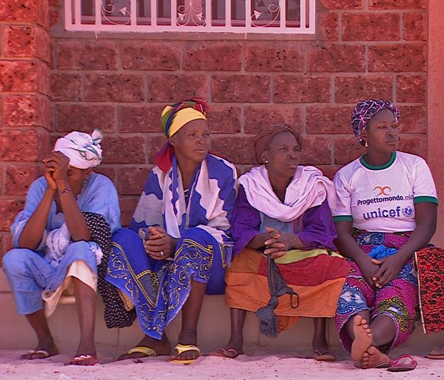 Women sit outside the hospital building
