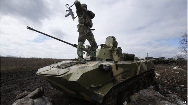 A Ukrainian soldier stands on an armoured vehicle at a military camp near the village of Michurino, Ukraine, 17 March 2014