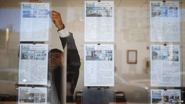 Vyacheslav Eshanu, head of Portugal Estate, places publicity notices on the glass wall of his office in Portimao on 11 November 2013.
