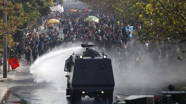 A police water cannon releases a jet of water on student protesters in Chile, April 2013