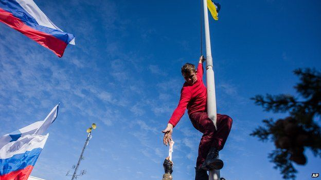 Pro-Russian activist takes down Ukraine's flag at Ukraine's navy HQ in Crimea on 19 March 2014