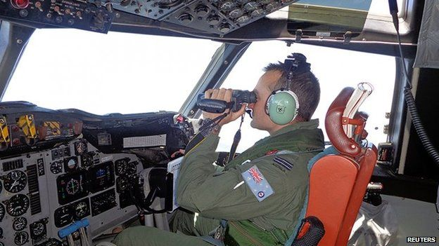 A Royal Australian Air Force pilot of an AP-3C Orion maritime patrol aircraft scans the surface of the sea near the west of Peninsula Malaysia in this handout picture by the Royal Australian Air Force on 17 March 2014