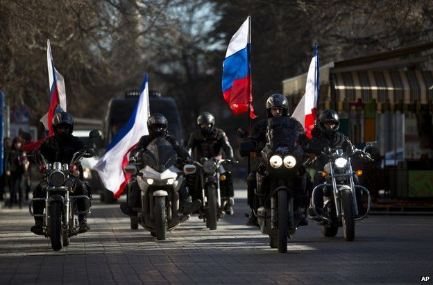 Bikers escort a van carrying the coffins of two men shot dead in Crimea, through the streets of Simferopol, 22 March