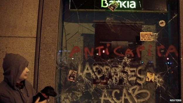 A man holds his dog while looking at a vandalised Bankia bank window following disturbances that broke out at the end of a demonstration