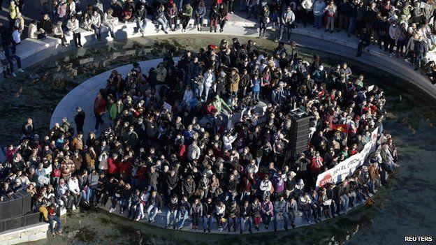 Anti-austerity demonstrators sit around a fountain in Colon square